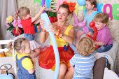 Five happy kids and facilitator make dogs of long balloons at children party. Inscription Happy Birt