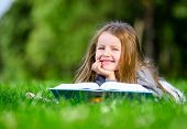 Little girl reads book lying on the green grass in the summer park