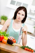 Woman with knife is going to cook breakfast from different groceries lying on the kitchen table