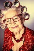 stock photo of hair curlers  - Portrait of an elderly woman in curlers looking at camera - JPG