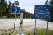 Lithuania country border sign between Latvia and Lithuania with coat of arms and flag.