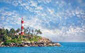 image of lighthouse  - Lighthouse on the rocks near the ocean at blue sky with clouds in Kovalam Kerala India - JPG