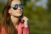 beautiful girl with sunglasses in dandelion field