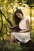 beautiful girl with book in the forest