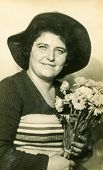 LODZ, POLAND - CIRCA 1960's: Vintage portrait of woman in a hat with a brim and with bunch of flowers