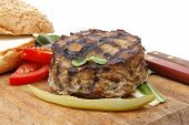 extra thick hot beef meat hamburger lunch on wooden plate with tomatoes and salad isolated on white