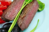 meat savory : grilled beef fillet mignon on blue plate with pepper chives and black greek olives ove