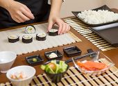 stock photo of rice  - Closeup of woman chef putting japanese sushi rolls with rice - JPG