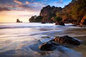 pic of volcanic  - Colorful sunset skies over the rocky volcanic coastline near Manuel Antonio National Park - JPG
