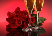 two champagne glasses with a dozen red roses in background