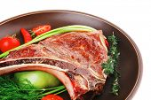 savory : roasted beef spare rib on dark dish with cutlery thyme pepper and tomato isolated over whit