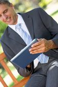 Tilt image of businessman using digital tablet in park