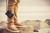 stock photo of foot  - Feet man and vintage retro photo camera outdoor Travel Lifestyle vacations concept