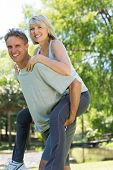 Portrait of loving man giving piggyback ride to woman in the park