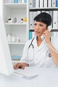 Concentrated female doctor using computer and telephone at medical office