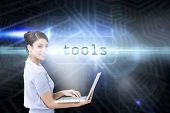 The word tools and cheerful businesswoman using a laptop against futuristic black and blue backgroun