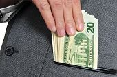 stock photo of bribery  - a man wearing a suit getting dollar bills in the pocket of his jacket - JPG