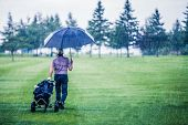 stock photo of sulky  - Golfer on a Rainy Day Leaving the Golf Course  - JPG