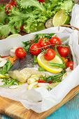 stock photo of cod  - Cod with lemon slices and vegetables  wrapped in baking parchment - JPG