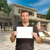 Man holding a blank, customizable message by a beautiful house
