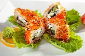 Maki Sushi with Smoked Eel, Fresh Cucumber, Salad Leaf, Cream Cheese and Prawn inside. Tobiko (flyin