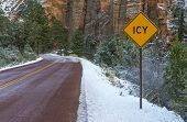 stock photo of icy road  - Landscape with road in winter forest and road sign ICY - JPG