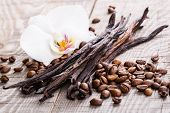 vanilla pods and coffee beans on wooden background