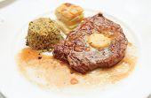Rib eye steak with bulgur, butter and potato gratin on plate