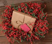 High angle view of a Christmas present wrapped with eco friendly craft paper and tied with twine. The package is resting on a field of red and green shredded crepe paper on rustic wood table.
