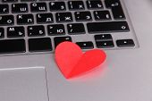 Red heart on computer keyboard close up
