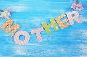 Mother- lettering of handmade paper letters on blue wooden background