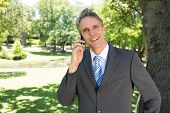 Portrait of happy businessman answering smart phone in park