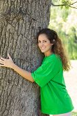 Portrait of smiling female environmentalist embracing tree trunk in park