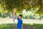 Full length portrait of a happy young boy holding kite at the park