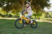 Full length portrait of a smiling young girl riding bicycle at the park