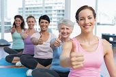 Portrait of smiling women gesturing thumbs up in the yoga class