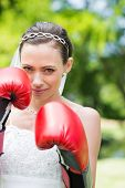 Portrait of woman in wedding dress wearing boxing gloves in park