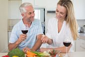 Cheerful couple making dinner together and drinking red wine at home in the kitchen
