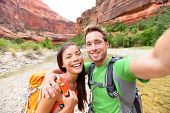 Travel hiking selfie self-portrait photo by happy couple on hike. Active lifestyle with hikers friends or lovers smiling at camera in Zion National Park, Utah, USA. Young Asian woman and Caucasian man