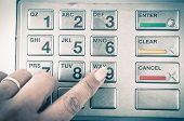 picture of automatic teller machine  - Closeup of finger pressing button in atm machine with metallic keyboard color toned - JPG