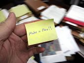 Messy office with hand holding note saying Make a Plan