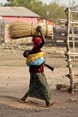 TORIT, SOUTH SUDAN-FEBRUARY 20 2013: Unidentified woman carries a heavy load on her head and her baby on her back in Torit, South Sudan