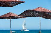 Sun Umbrellas And Sailboat At Sea