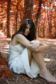Sad Woman Sitting In Forest With Red Leaves