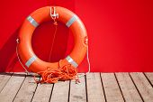 foto of lifeguard  - Lifebuoy stands on wooden floor nearby red wall of lifeguard station - JPG