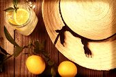 Fresh Squeezed Lemonade on a rustic wooden table with lemons and a sun hat. Horizontal format with a