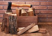Box of firewood and axe on floor on brick background