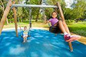 Boy and girl singing on swings