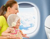 stock photo of aeroplane  - Happy mother and kid traveling together in aeroplane cabin near window - JPG