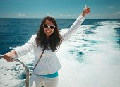 happy Woman enjoying a sunny summer day on a boat; position inspires freedom.